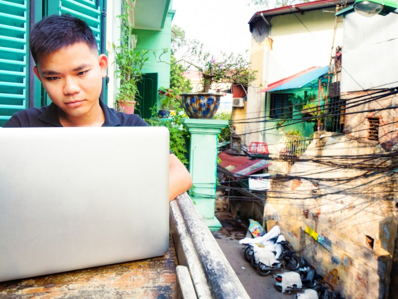 A young Vietnamese man working on a laptop on a Hanoi balcony. Photo: iStock/Getty Images