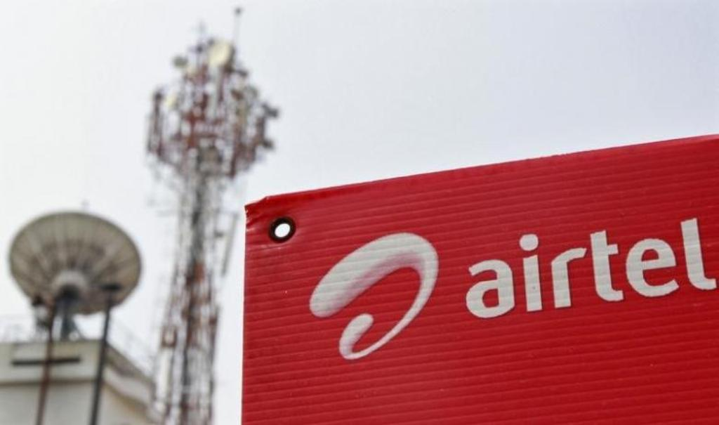 A Bharti Airtel billboard against the backdrop of company's telecommunication tower in Kochi _ Reuters