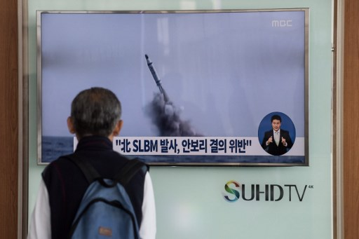 A man watches a television news channel in Seoul showing footage of North Korean submarine-launched ballistic missile (SLBM). Photo: AFP