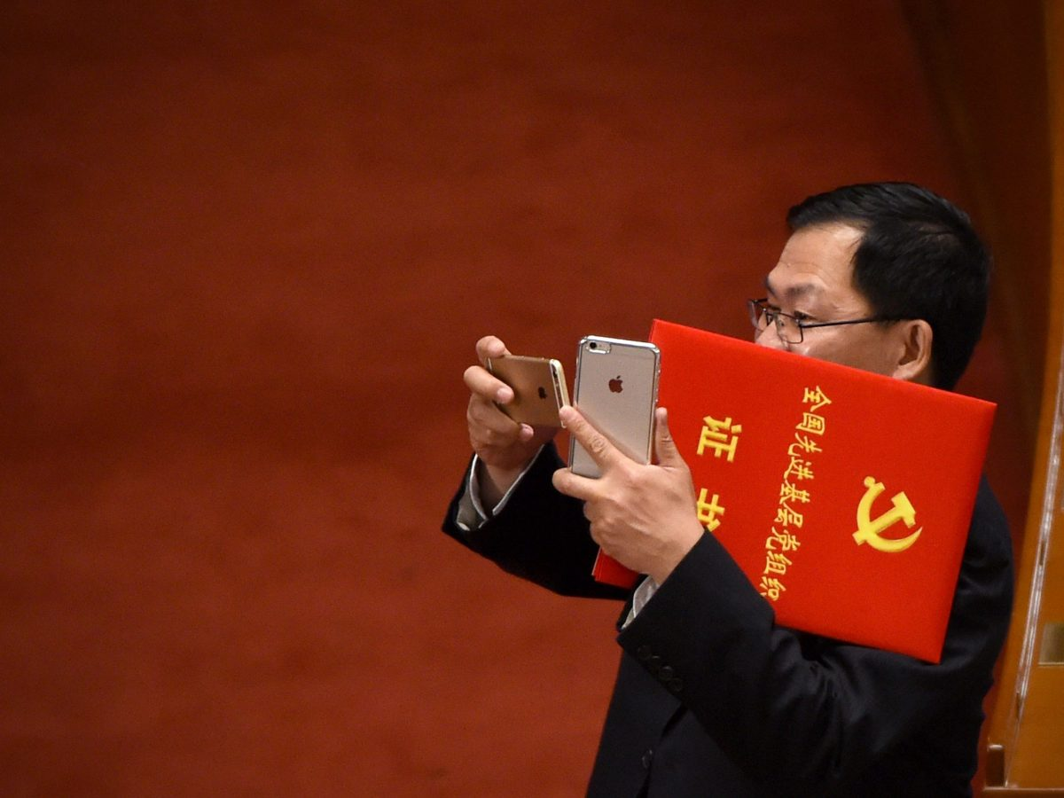 A Chinese party member uses a mobile phone to take a photo during the Celebration Ceremony of the 95th Anniversary of the Founding of the Communist Party of China at the Great Hall of the People in Beijing on July 1, 2016. Photo: AFP / Wang Zhao
