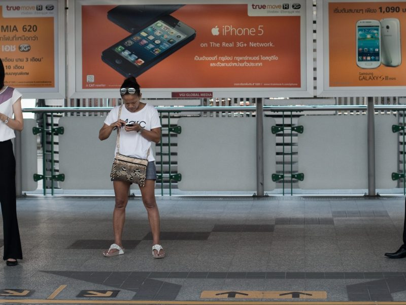 People look at their smartphones while waiting for a train at a BTS station in Bangkok. Photo: AFP / Nicolas Asfouri