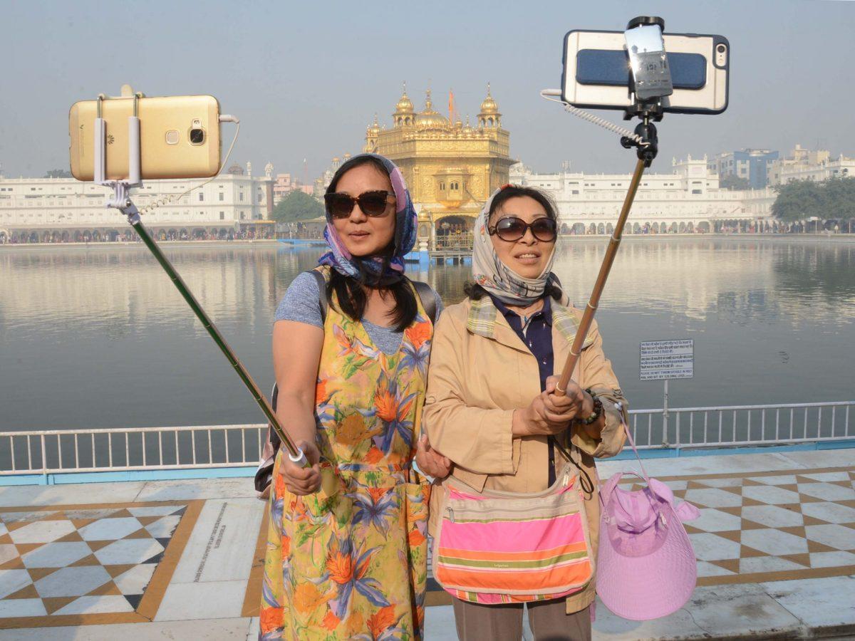 Chinese tourists take a 'selfie' at the Golden Temple in Amritsar on November 14, 2016, as Sikh devotees mark the 547th birth anniversary of Sri Guru Nanak Dev. Photo: AFP / Narinder Nanu
