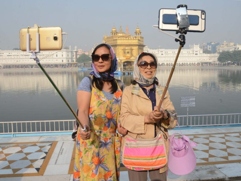 Chinese tourists take a 'selfie' at the Golden Temple in Amritsar on November 14, 2016, as Sikh devotees mark the 547th birth anniversary of Sri Guru Nanak Dev. Photo: AFP / Narinder Nanu