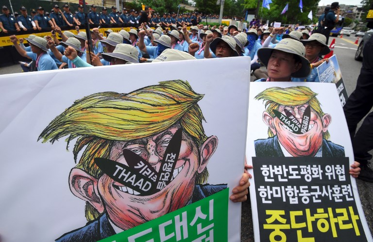 South Korean protestors hold placards showing a caricature of US President Donald Trump during an anti-US rally to condemn Trump, outside a US Army base in Seoul on August 14, 2017. Photo: AFP: Jung Yeon-Je
