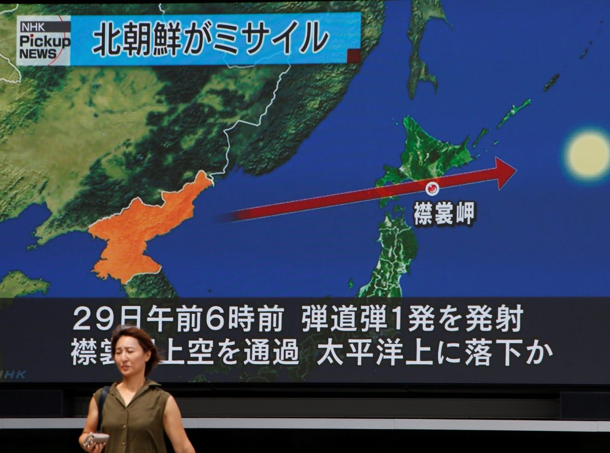 A woman walks past a TV screen in Tokyo showing news of North Korea's missile launch over Japan August 29, 2017.  Reuters/Kim Kyung-Hoon
