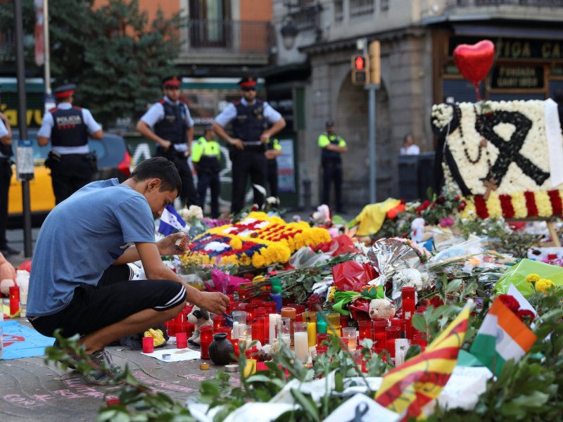 A man lights a candle on August 21, 2017, at an impromptu memorial where a van crashed into pedestrians at Las Ramblas in Barcelona. Photo: Reuters/Susana Vera