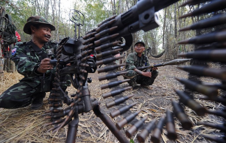 Karen National Union (KNU) soldiers stand guard with their assault weapons at Oo Kray Kee village in Karen State near Thai-Myanmar border on January 30, 2012. The Karen National Union (KNU) is waging the world's longest-running insurgency, launched 63 years ago, shortly after the nation then known as Burma won its independence from Britain in 1948.   AFP PHOTO/PORNCHAI KITTIWONGSAKUL / AFP PHOTO / PORNCHAI KITTIWONGSAKUL