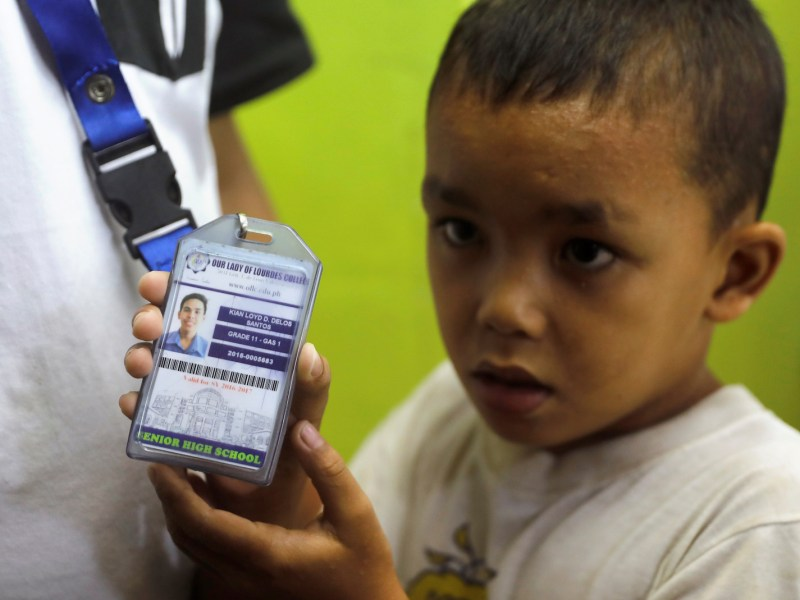 A boy shows the media a school ID card of Kian Loyd delos Santos, a 17-year-old high school student, who was among the 91 people shot dead this week in an escalation of President Rodrigo Duterte's ruthless war on drugs in Caloocan city, Metro Manila, Philippines August 18, 2017. Photo:  Reuters/Erik De Castro