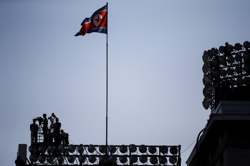 Cameramen film under the North Korean flag during a parade celebrating the 70th anniversary of the founding of the ruling Workers' Party of Korea, in Pyongyang, on October 10, 2015. Photo: Reuters / Damir Sagolj