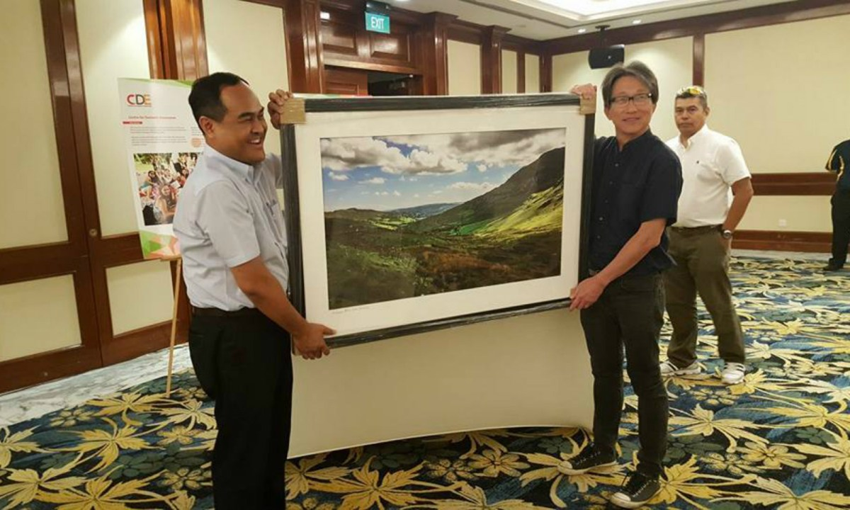 CDE executive director Shamsul Kamar (left) and Manpower Minister Lim Swee Say hold a photograph shot by Tan Chuan-Jin. Photo: Facebook / Shamsul Kamar