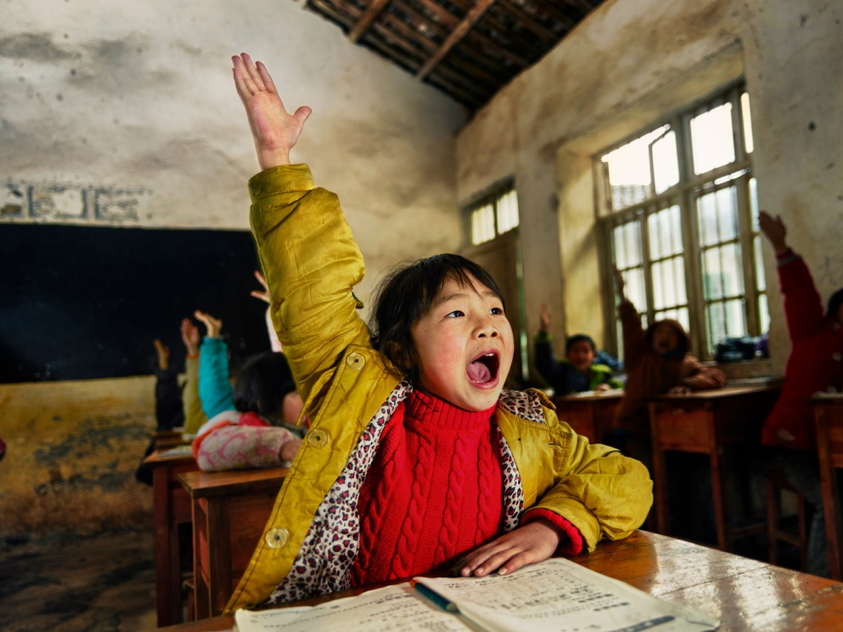 Chinese school children raising hands to answer a classroom question. Photo: iStock/Getting Images