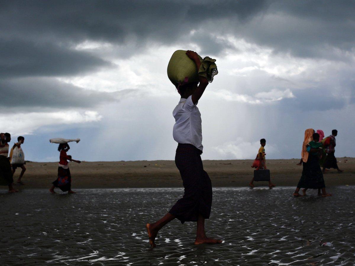 Rohingya refugees walk on the shore after crossing the Bangladesh-Myanmar border by boat through the Bay of Bengal in Shah Porir Dwip, Bangladesh September 11, 2017. Photo: Reuters/Danish Siddiqui