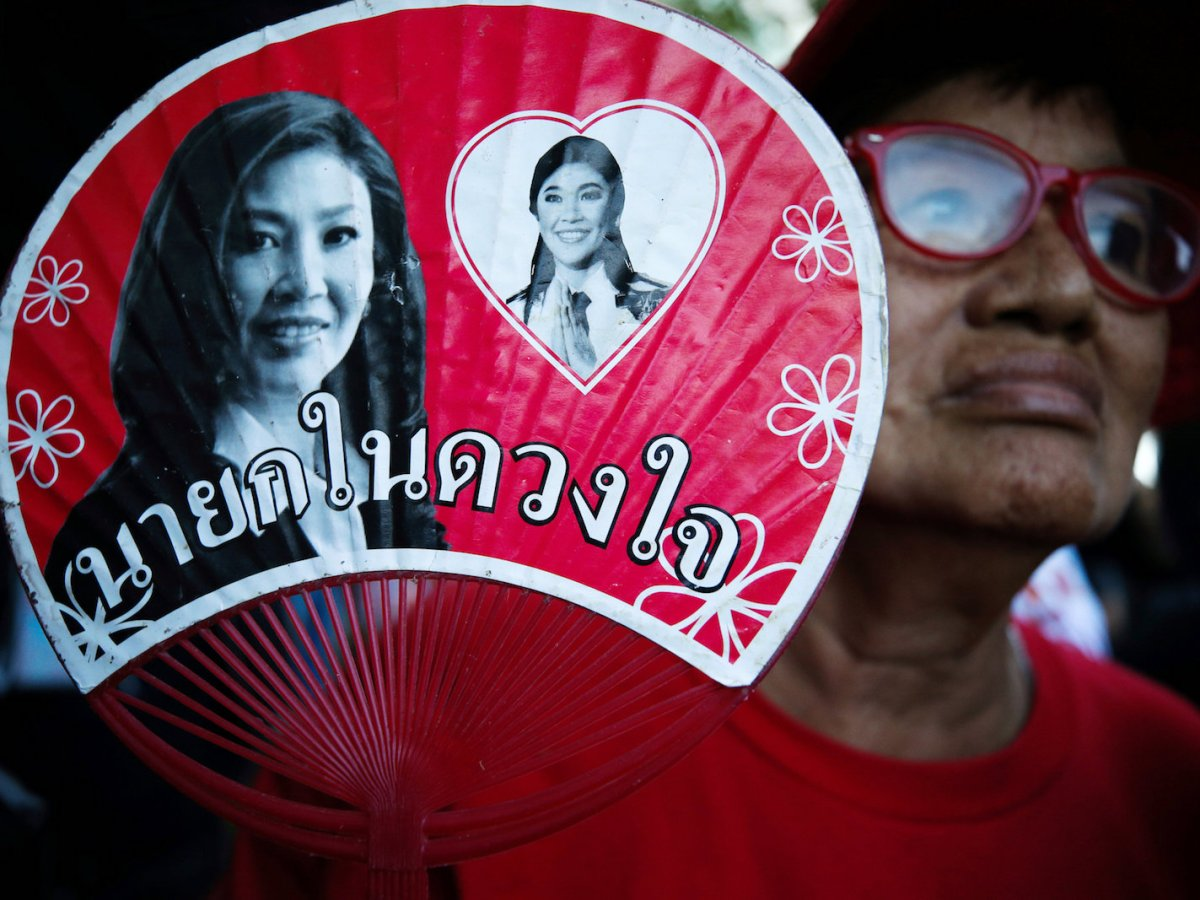 A 'Red Shirt' supporter holds a picture of of ousted former Thai Prime Minister Yingluck Shinawatra while waiting for the verdict in a negligence trial involving Yingluck at the Supreme Court in Bangkok, Thailand, September 27, 2017. Photo: Reuters/Athit Perawongmetha