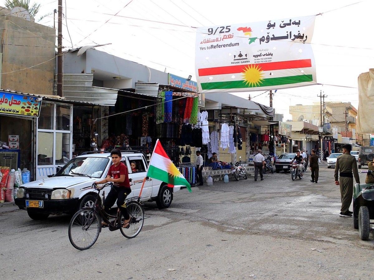 A boy rides a bicycle with the flag of Kurdistan in Tuz Khurmato, Iraq on Sept. 24, 2017. Photo: Reuters/Thaier Al-Sudani