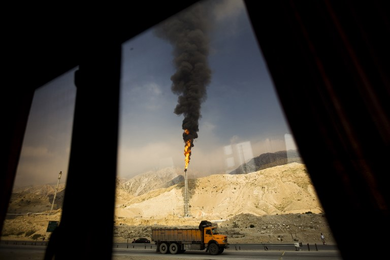 A gas flame is seen through a bus window in the South Pars gas field facilities in the southern Iranian port of Assaluyeh. Photo: AFP/Behrouz Mehri