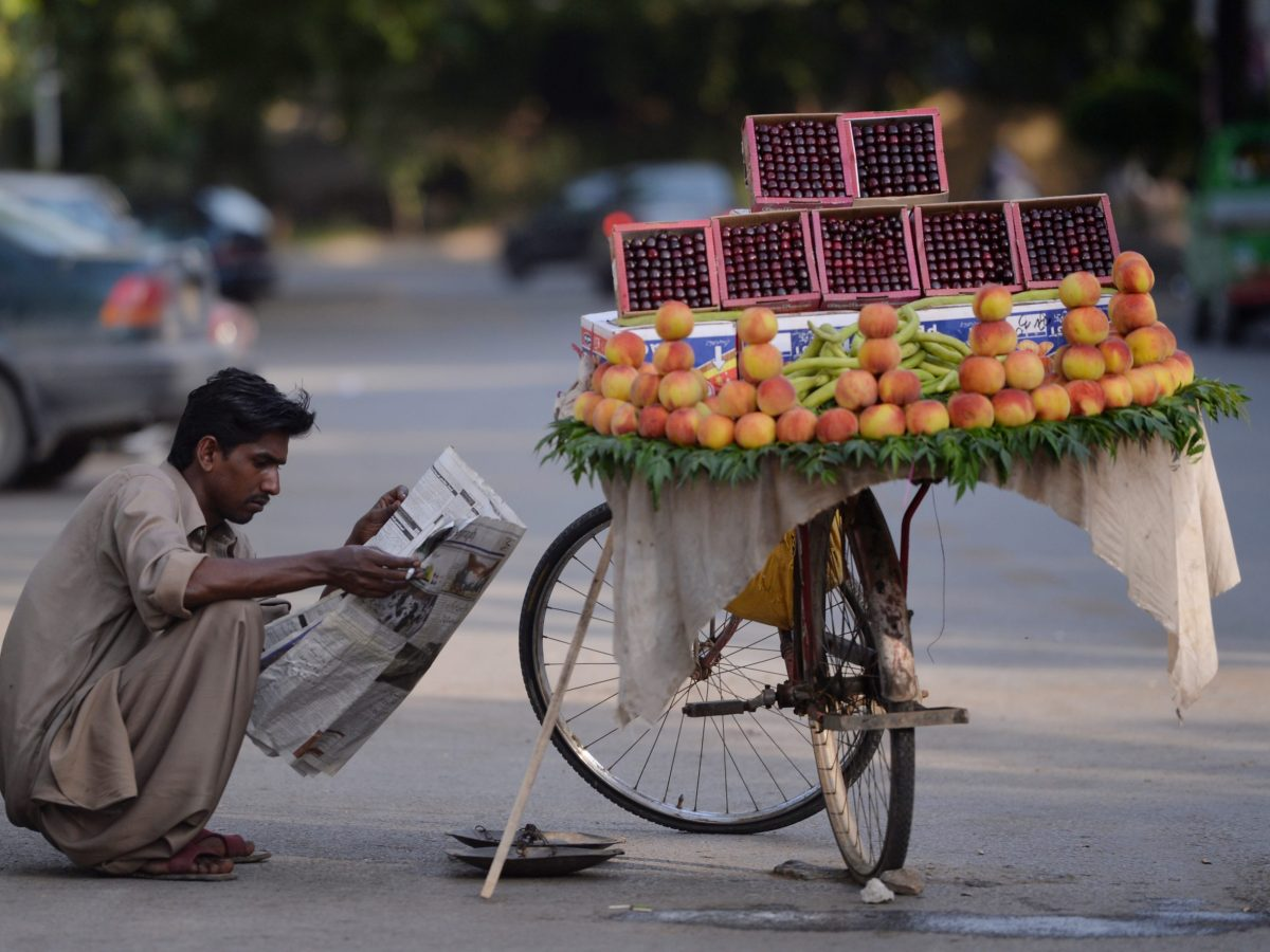 A Pakistani fruit vendor reads a newspaper as he waits for customers on a street in Islamabad. Photo: AFP / Aamir Qureshi