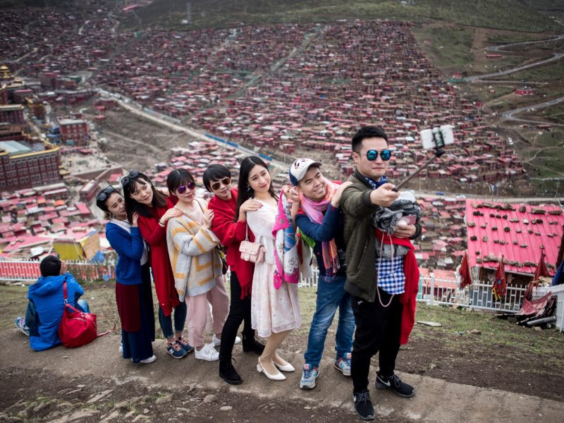 Chinese tourists posing for a selfie overlooking partially demolished houses at the Larung Gar Buddhist Institute in Sertar county in southwest China's Sichuan province. Photo: AFP / Johannes Eisele