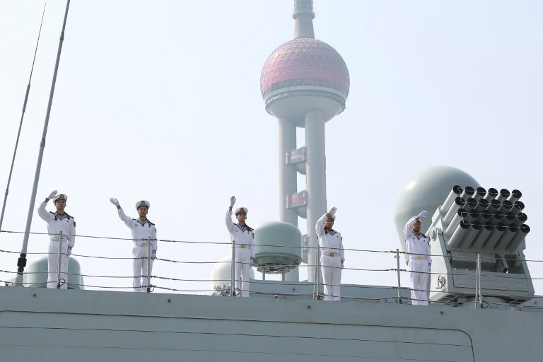 Chinese PLA soldiers at a naval ship for a voyage to some 20 countries wave to the public on the Huangpu river in Shanghai. Photo: AFP