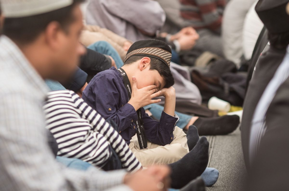 A young boy battles fatigue during Friday prayers with the exiled Caliph Mirza Masroor Ahmad, the spiritual leader of the Ahmadiyya Muslim Community, on the grounds of a future mosque in Raunheim, Germany, on 14 April 2017. Photo: Frank Rumpenhorst / DPA