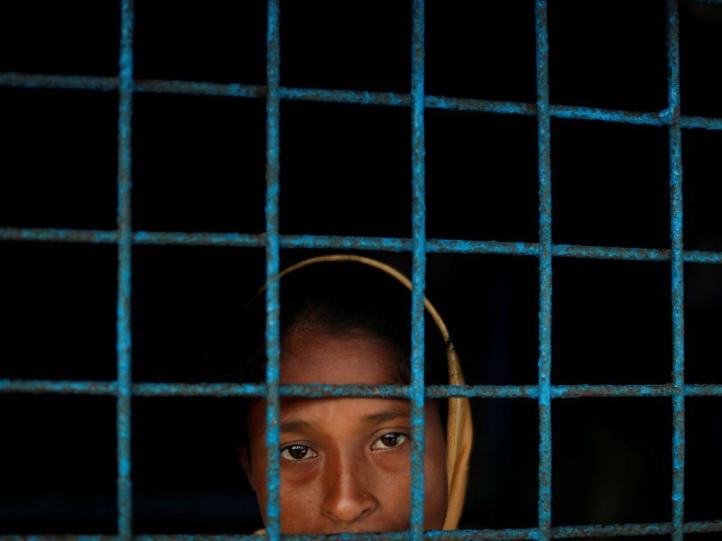 A Rohingya refugee who crossed the border from Myanmar this week stands at a window of a school used as a shelter at Kotupalang refugee camp near Cox's Bazar, Bangladesh October 20, 2017. Photo: Reuters/Jorge Silva