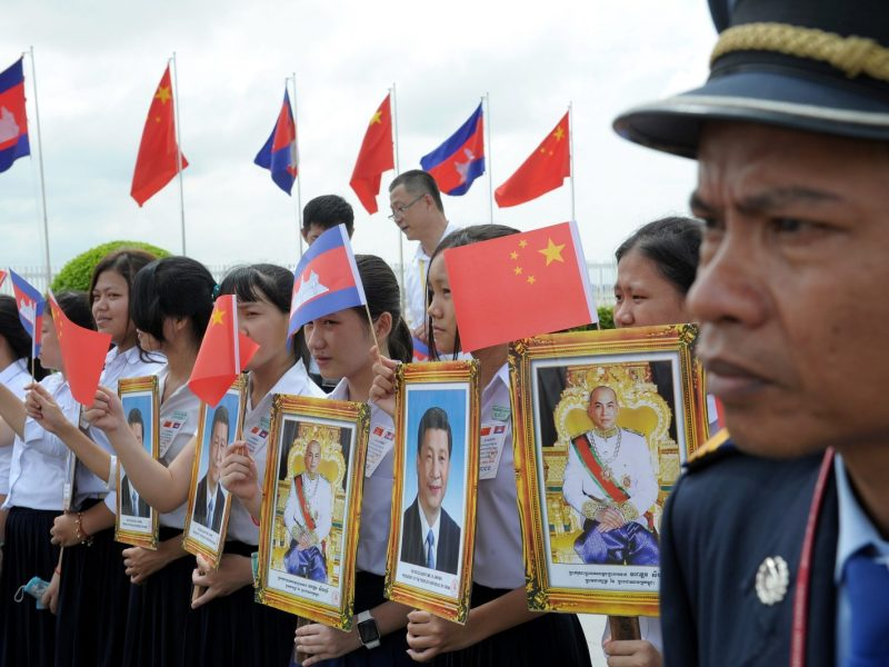 A Cambodian police official stands guard as students hold portraits of China's President Xi Jinping and King Norodom Sihamoni during Xi's arrival at the Phnom Penh international airport on October 13, 2016. Photo: AFP/Tang Chhin Sothy