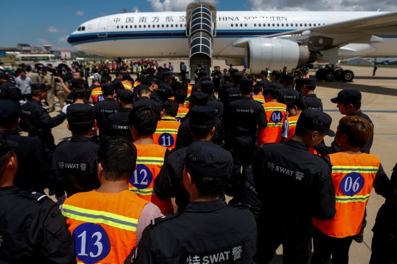 Chinese nationals (in orange vests) who were arrested over a suspected Internet scam are escorted by Chinese police before being deported at Phnom Penh International Airport on October 12, 2017. Photo: Reuters / Samrang Pring