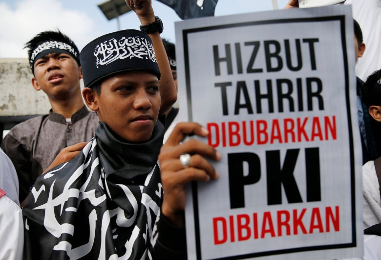 "An Islamist group member holds a poster during an anti-communist protest outside parliament building in Jakarta, Indonesia, September 29, 2017. Poster reads, ""Hizbut Tahrir dissolved, Indonesia's Communist Party (PKI) allowed"". Photo: Agencies"
