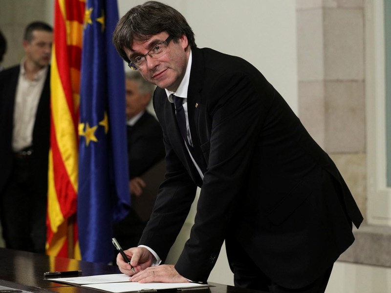 Catalan President Carles Puigdemont signs a declaration of independence at the Catalan regional parliament in Barcelona, on October 10, 2017. Photo: Reuters/Albert Gea
