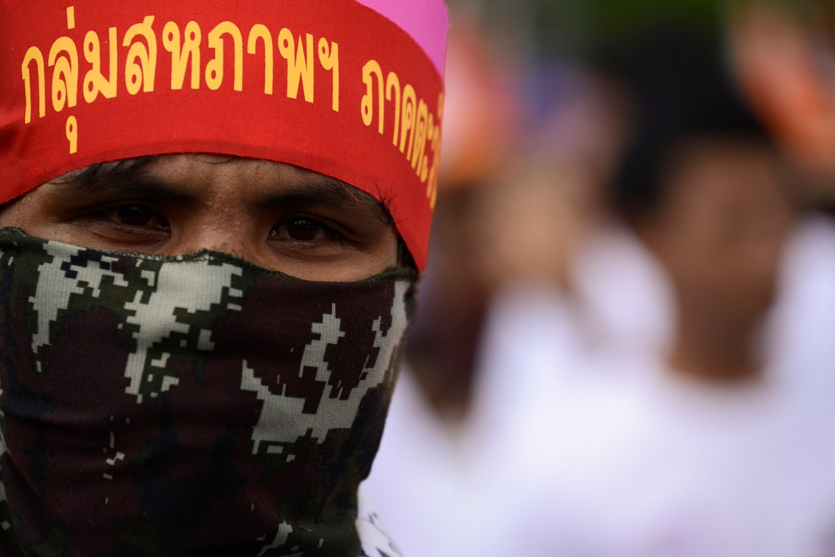 Thai workers hold a placard as they rally to mark the international worker's day in on 1st May 2017 in Bangkok. Photo: NurPhoto via AFP/Anusak Laowilas