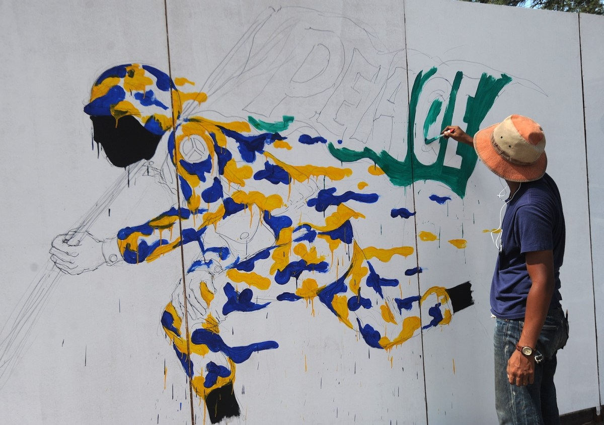 An artist takes part in a graffiti event as part of the Saiburi Street Xhibit in Pattani - one of Thailand's southernmost Muslim majority provinces hit by a deadly insurgency - on February 28, 2016. Photo: AFP/Madree Tohlala