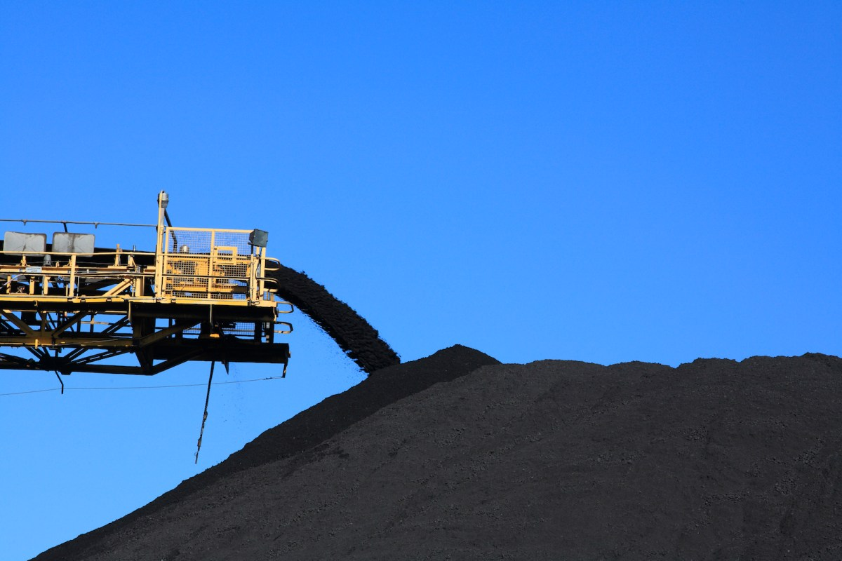 a large yellow conveyor belt carrying coal and emptying onto a huge pile.