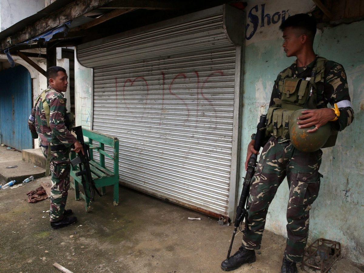 """Philippine soldiers stand guard in front of a door spray painted with """"I love ISIS"""" graffiti after government troops cleared the area from pro-Islamic State militant groups inside the war-torn Marawi city, southern Philippines October 19, 2017. Photo: Reuters/Romeo Ranoco"""
