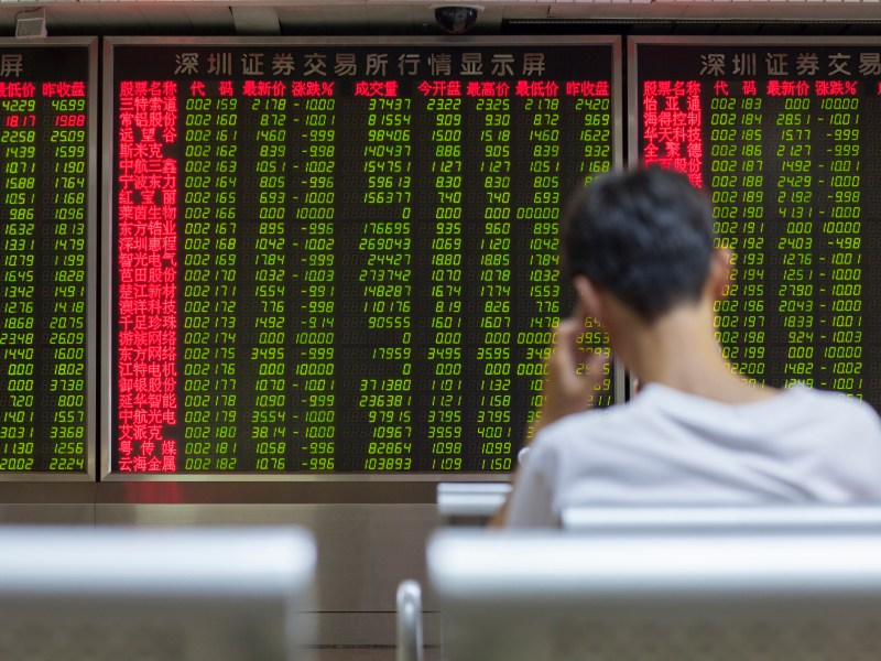 Chinese citizen watching stock information at a Beijing open-to-the-public municipal access market trading exchange room facility during a stock market index decline in China. Photo: iStock