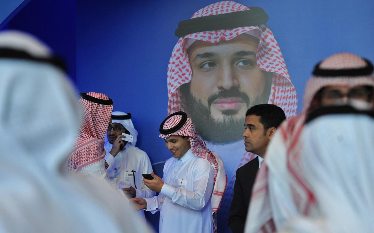 """Saudi men chat in front of a poster of Saudi Crown Prince Mohammed bin Salman during the """"MiSK Global Forum"""" held under the slogan """"Meeting the Challenge of Change"""" in Riyadh, on November 15, 2017. Photo: AFP / Fayez Nureldine"""