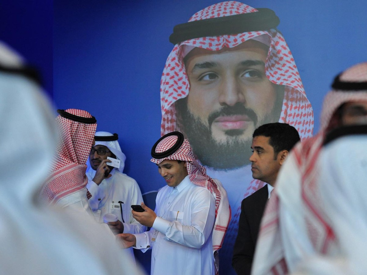 "Saudi men chat in front of a poster of Saudi Crown Prince Mohammed bin Salman during the ""MiSK Global Forum"" held under the slogan ""Meeting the Challenge of Change"" in Riyadh, on November 15, 2017. Photo: AFP / Fayez Nureldine"