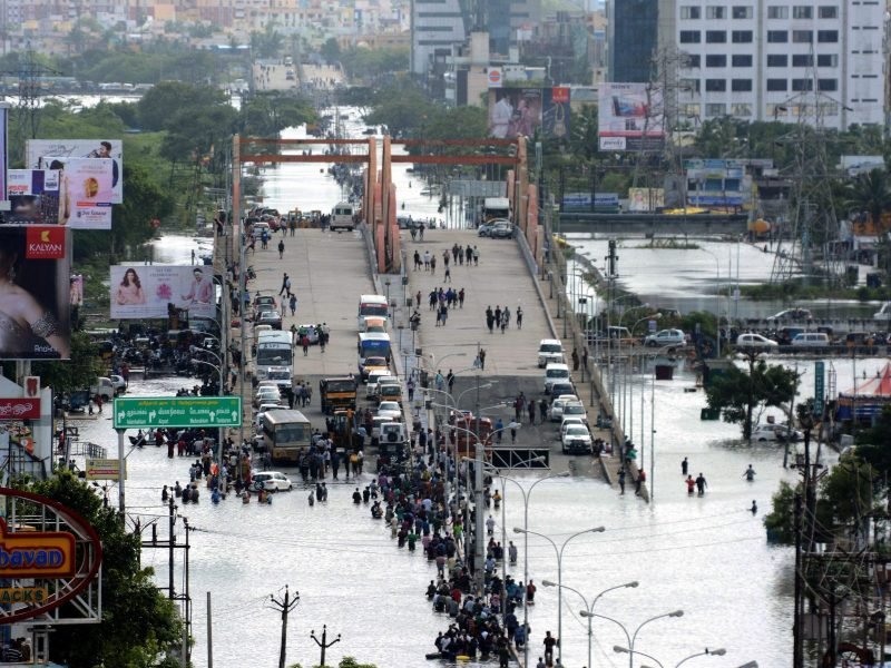 Indian residents and motorists gather on a flyover as others wade through floodwaters in Chennai on December 3, 2015. Photo: AFP / Strdel