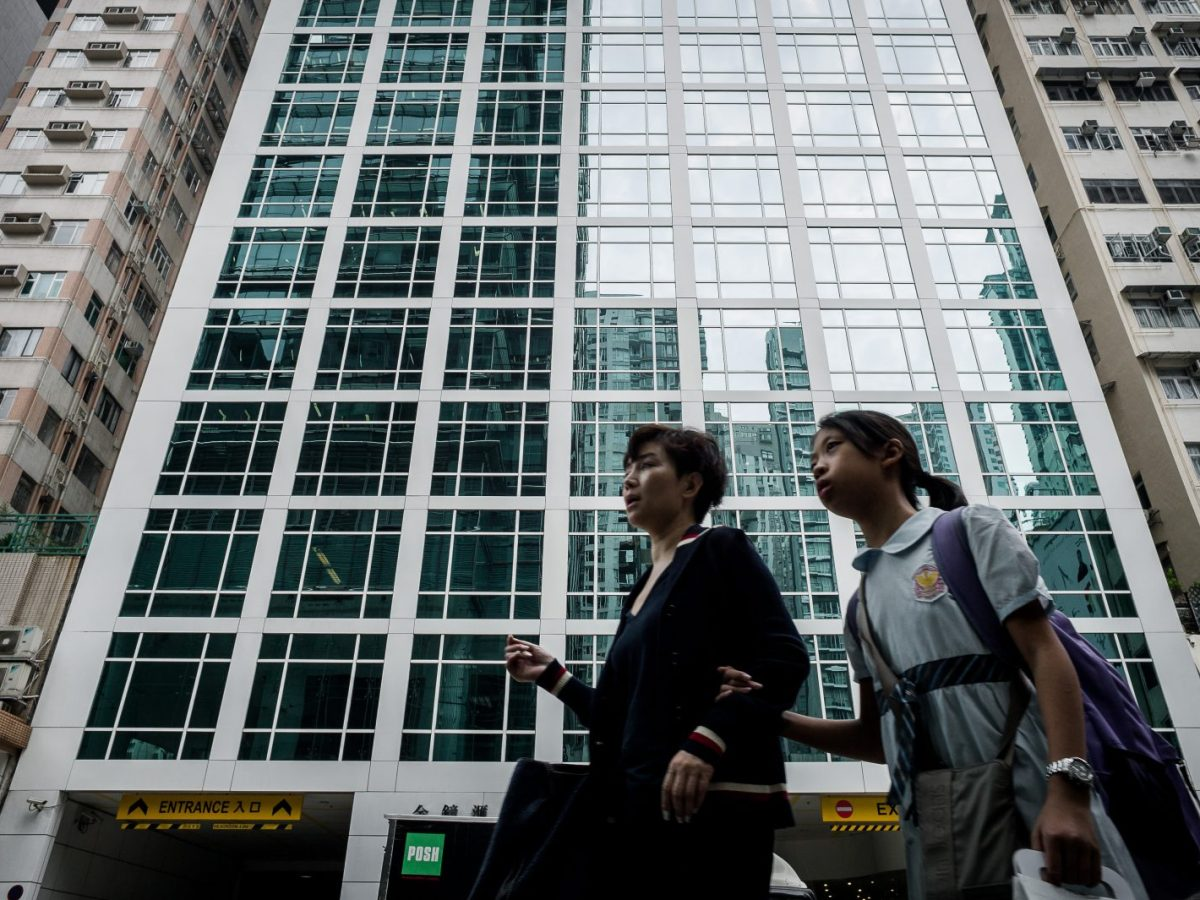 A woman and her daughter cross the street in front of a high-rise building in Hong Kong. Photo: AFP / Philippe Lopez