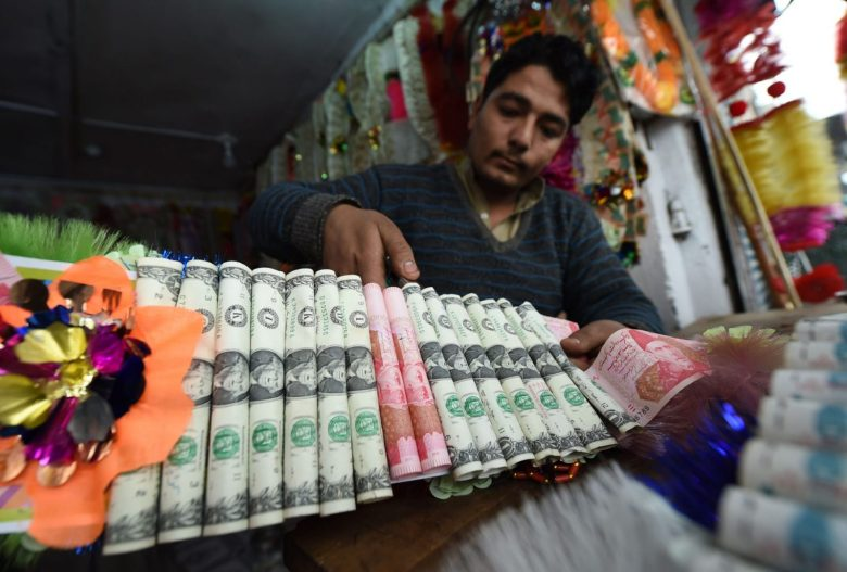 A shopkeeper makes garlands with US dollars and rupee notes at a flower market in Peshawar. Photo: AFP/Abdul Majeed