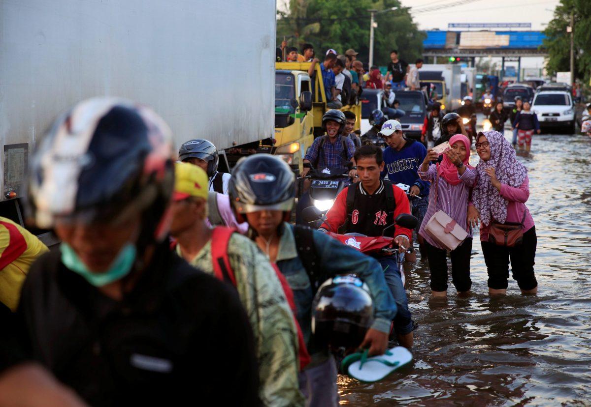 Commuters walk through flooded street after high tide hit Muara Baru area in Jakarta, Indonesia, December 6, 2017.  Photo: Reuters / Beawiharta