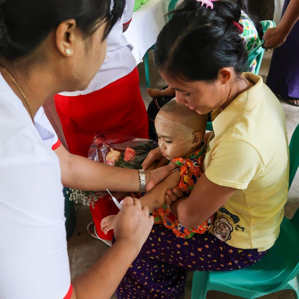 A Burmese mother holds her child as a health worker gets ready to give another vaccination.  Photo: Gavi.
