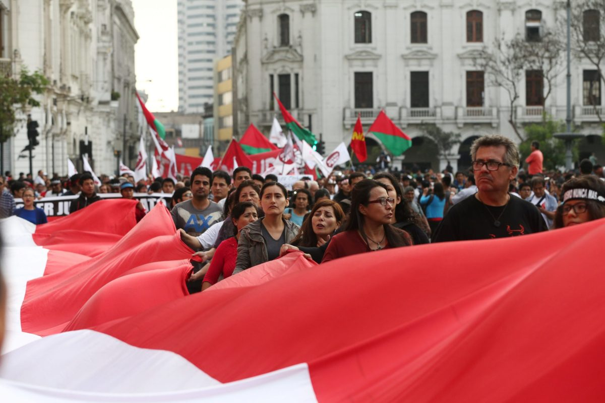People hold a banner with the colours of the Peruvian flag as they march against President Pedro Pablo Kuczynski's pardon for former president Alberto Fujimori in Lima, Peru on December 28, 2017. Photo: Reuters / Mariana Bazo