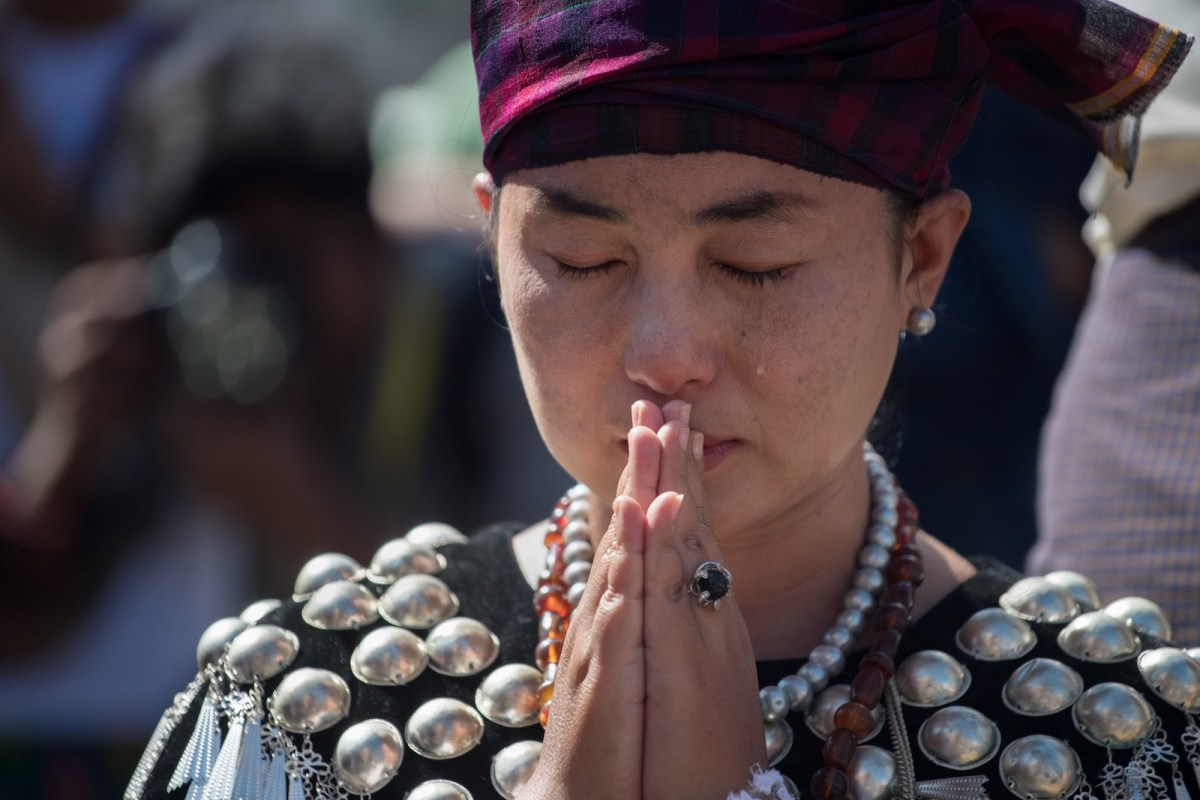 A woman wearing traditional dress from Kachin state in Myanmar sheds a tear as she prays outside St. Mary's Cathedral during a mass led by Pope Francis in Yangon on November 30, 2017. Photo: AFP