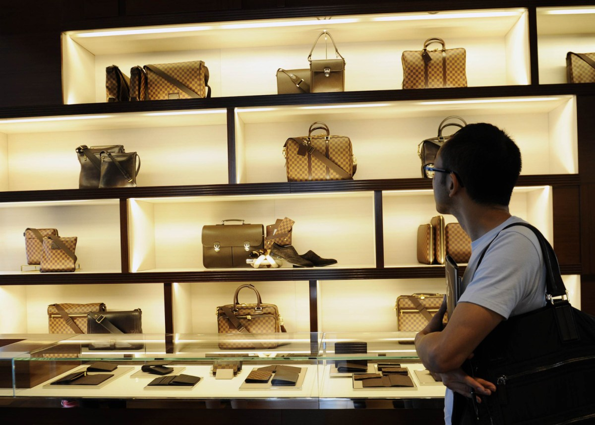 A Singaporean shopper looks at a collection of Louis Vuitton bags and wallets at the French company's nautical concept store at Singapore's Marina Bay Sands casino complex. Photo: AFP/Simin Wang