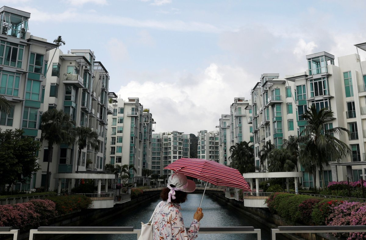 A woman passes a private condominium estate in Singapore February 13, 2017. Photo: Reuters/Edgar Su