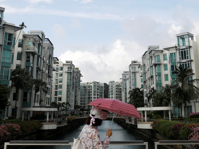 A woman passes a private condominium estate in Singapore February 13, 2017. Photo: Reuters/Edgar Su