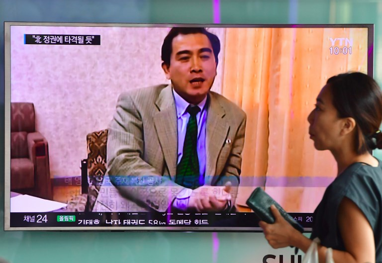 A woman walks past a television screen showing Thae Yong-Ho, North Korea's then ambassador to Britain, seen now as one of the highest-ranking North Korean officials to ever defect. Photo: AFP/Jung Yeon-je