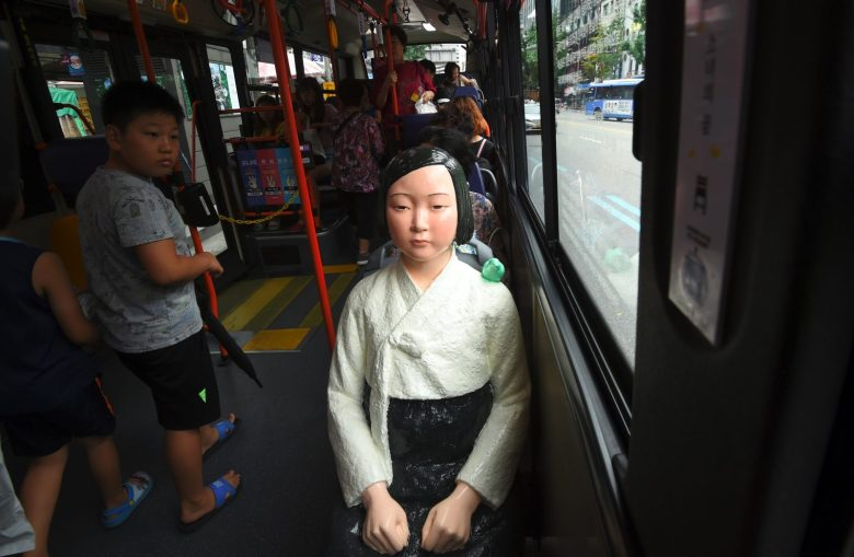 """A boy (looks at a statue of a teenage girl symbolizing """"comfort women"""" on a bus running through downtown Seoul on August 14, 2017.Photo: AFP / Jung Yeon-Je"""