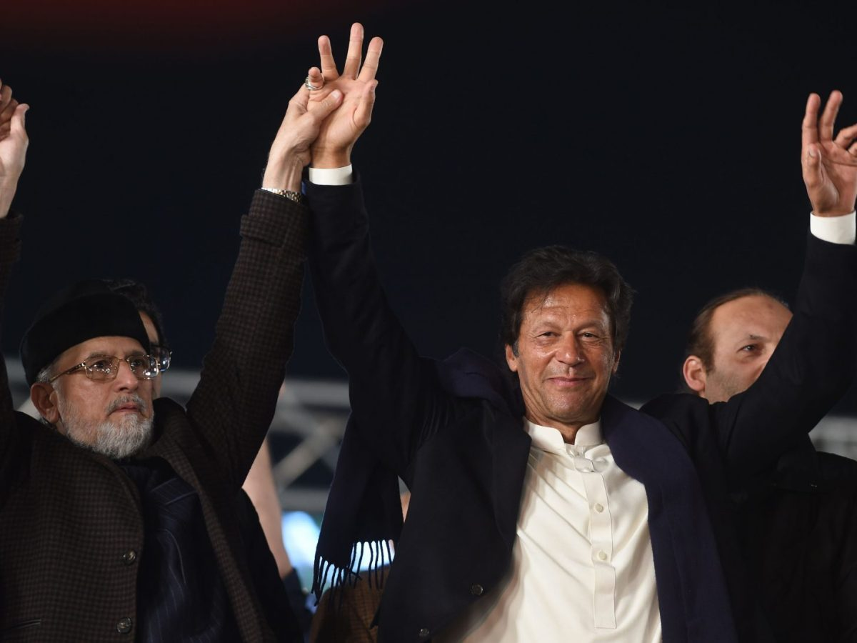 Tahir-ul Qadri (left) of Pakistan Awami Tehreek (PAT), and Pakistan Tehreek-i-Insaf (PTI)  leader Imran Khan join hands at an anti-government rally in Lahore on January 17, 2018. Photo: AFP / Arif Ali