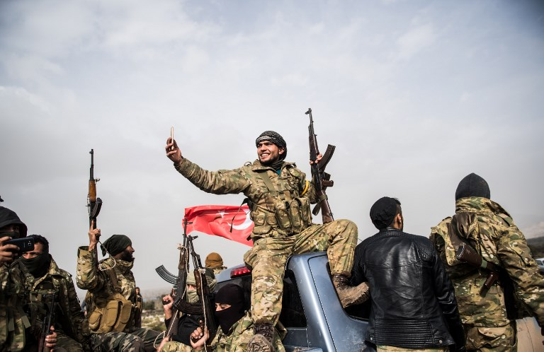 A Syrian opposition fighter takes a selfie as fighters walk through Syria in front of Turkish troops near the Syrian border at Hassa, Hatay province, on January 22, 2018. Photo: AFP/Bulent Kilic