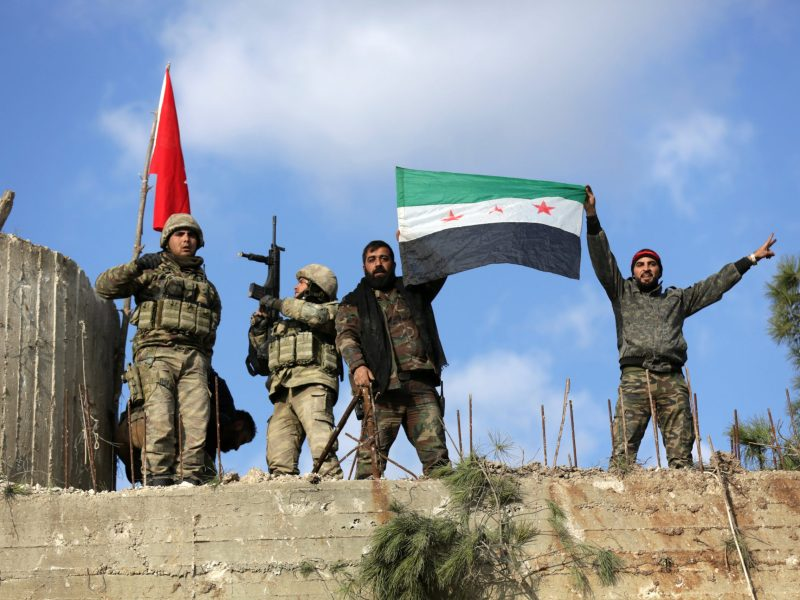 Turkish forces and Free Syrian Army members hold flags on Mount Barsaya, northeast of Afrin, Syria January 28, 2018. Photo: Reuters/Khalil Ashawi
